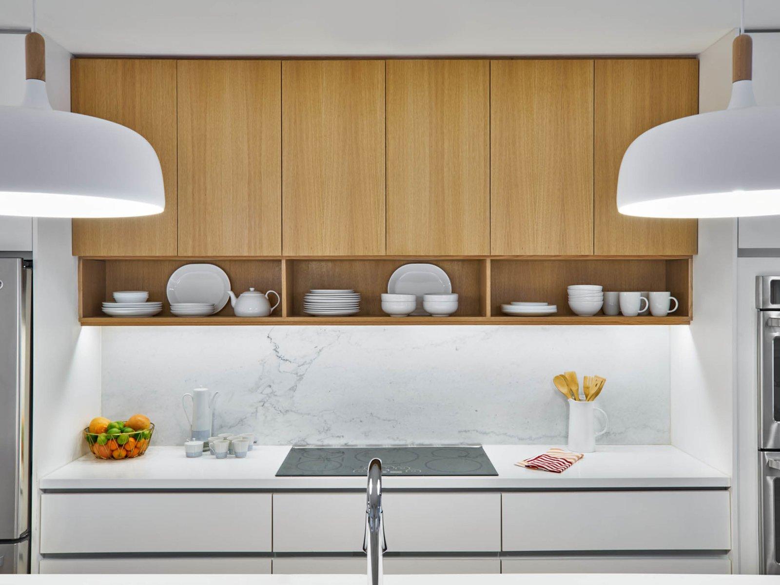 Kitchen, Marble Counter, Wood Cabinet, White Cabinet, Stone Slab Backsplashe, and Pendant Lighting Kitchen  The Historic Ely Building