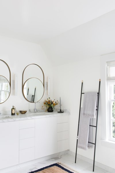 Master bathroom with modern round mirrors and towel ladder.