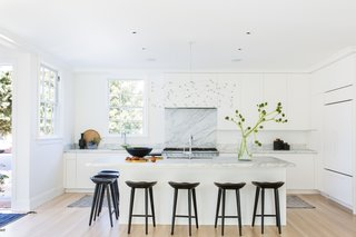 Kitchen with white panel cabinetry, marble counters and black bar stools.
