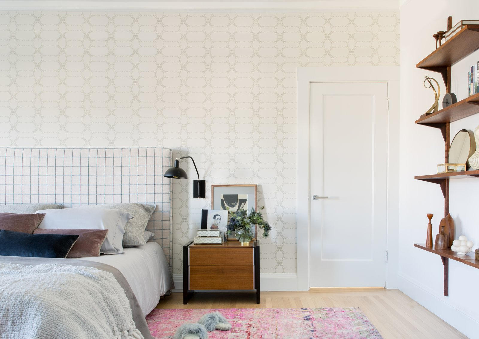 Bedroom, Shelves, Light Hardwood Floor, Night Stands, Wall Lighting, and Bed Master bedroom with patterned headboard and wallpaper.  Sea Cliff Preppy Contemporary