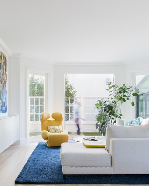 Family room with yellow Wink chair, navy rug and custom sectional.
