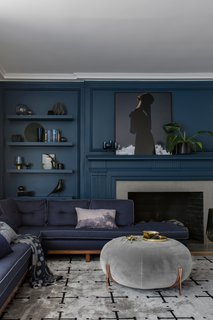Living room with tone-on-tone navy walls and sofa.