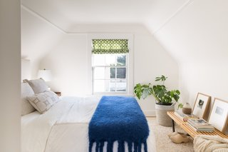 Guest bedroom with white bedding and bright blue throw.