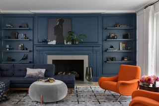 Living Room with tone-on-tone navy walls and and accent chairs upholstered in Hermes fabric.