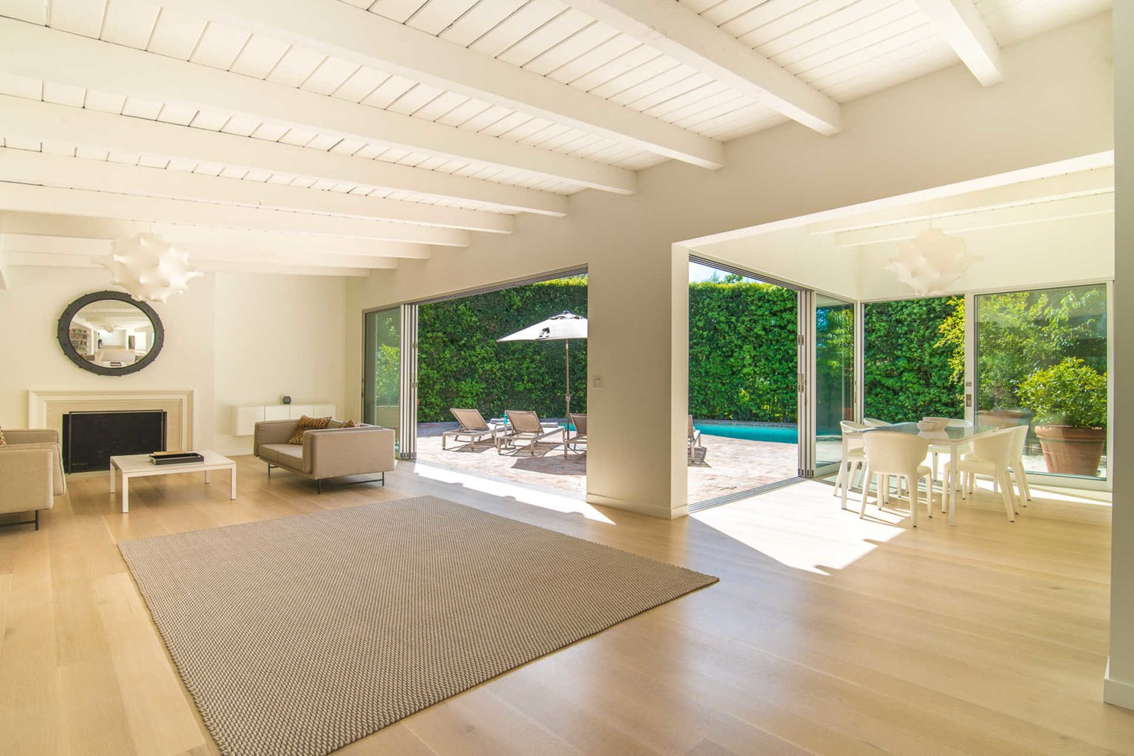 An open, light-filled living room with a fireplace and exposed beams is designed for embracing the quintessential California lifestyle, with sliding walls of glass to a fully-hedged swimming pool.  Nichols Canyon
