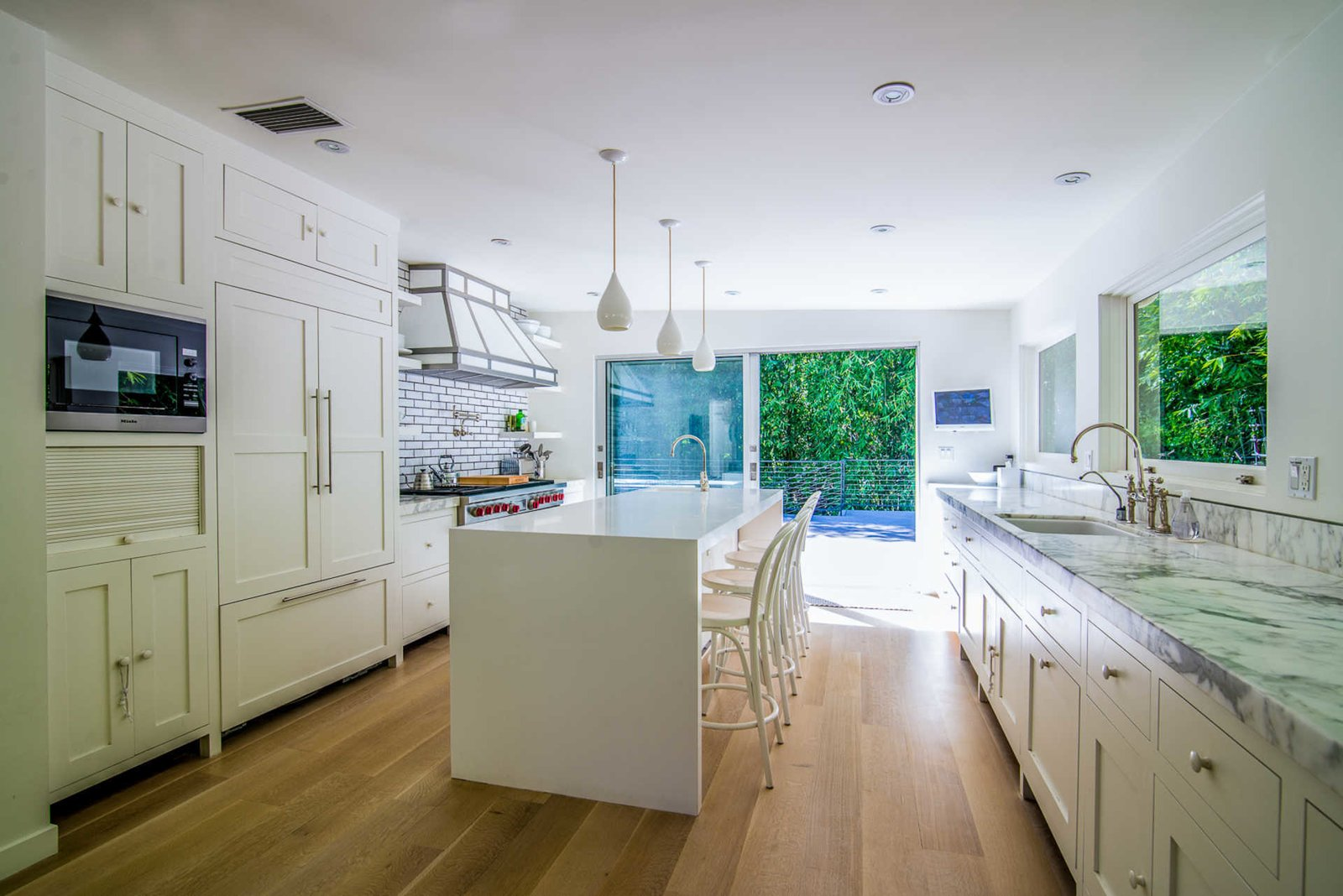 A spacious chef's kitchen features Calacatta marble countertops, Wolf and Miele appliances, a large eat-in island, and sliding walls of glass to an expansive rear deck for entertaining.  Nichols Canyon