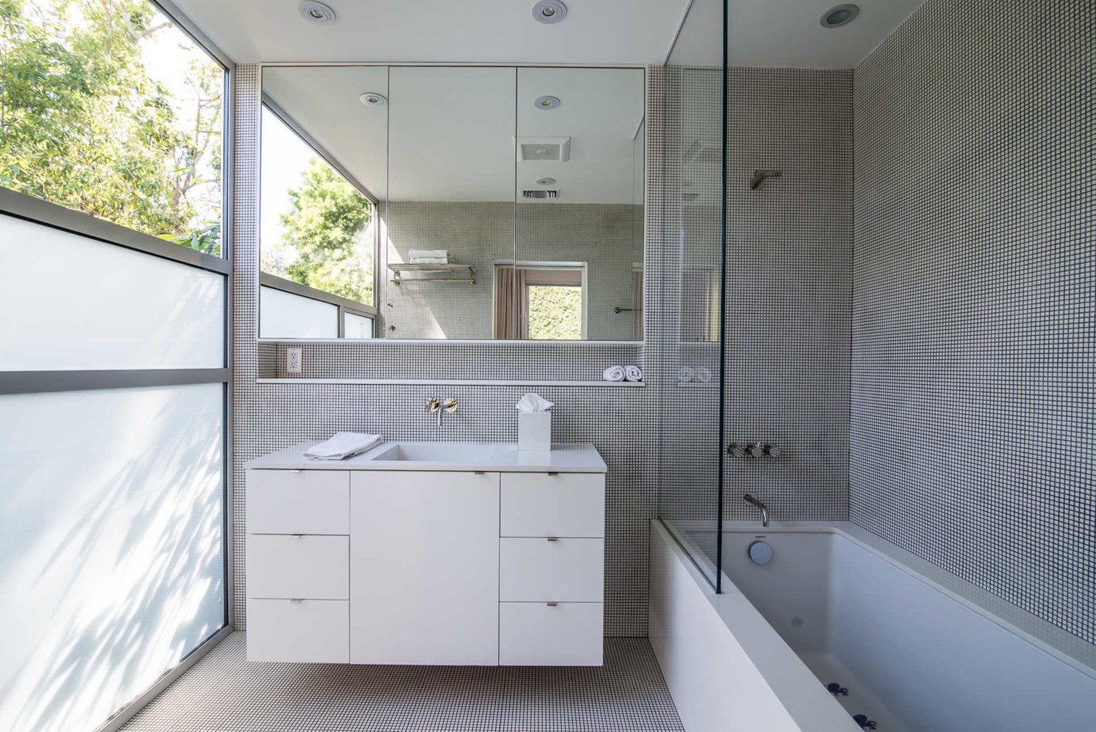 The home was thoughtfully designed to take full advantage of the property's idyllic surroundings. A serene guest bathroom features a frosted wall of glass and clerestory window, inspiring a gracious play on light and shadow.  Nichols Canyon