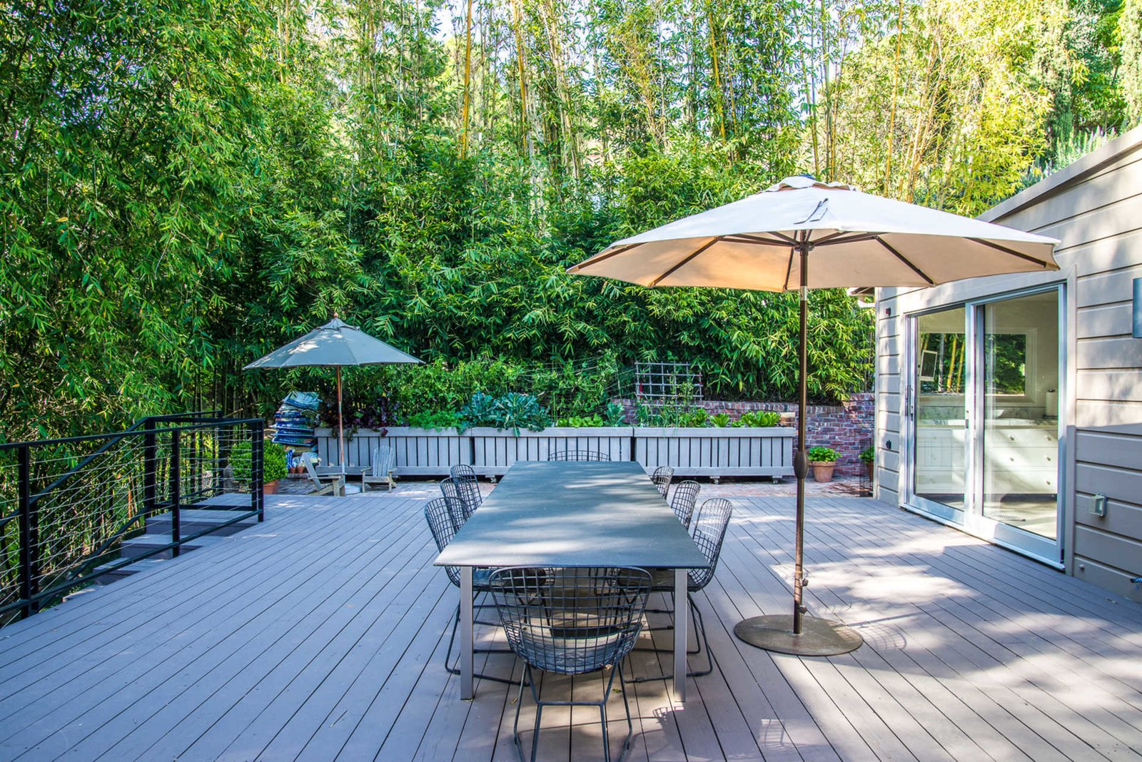 An expansive rear deck surrounded by lush bamboo hedges is a tranquil retreat for dining and lounging. Sliding pocket doors off the kitchen and bedrooms create a seamless connection with the outdoors.  Nichols Canyon
