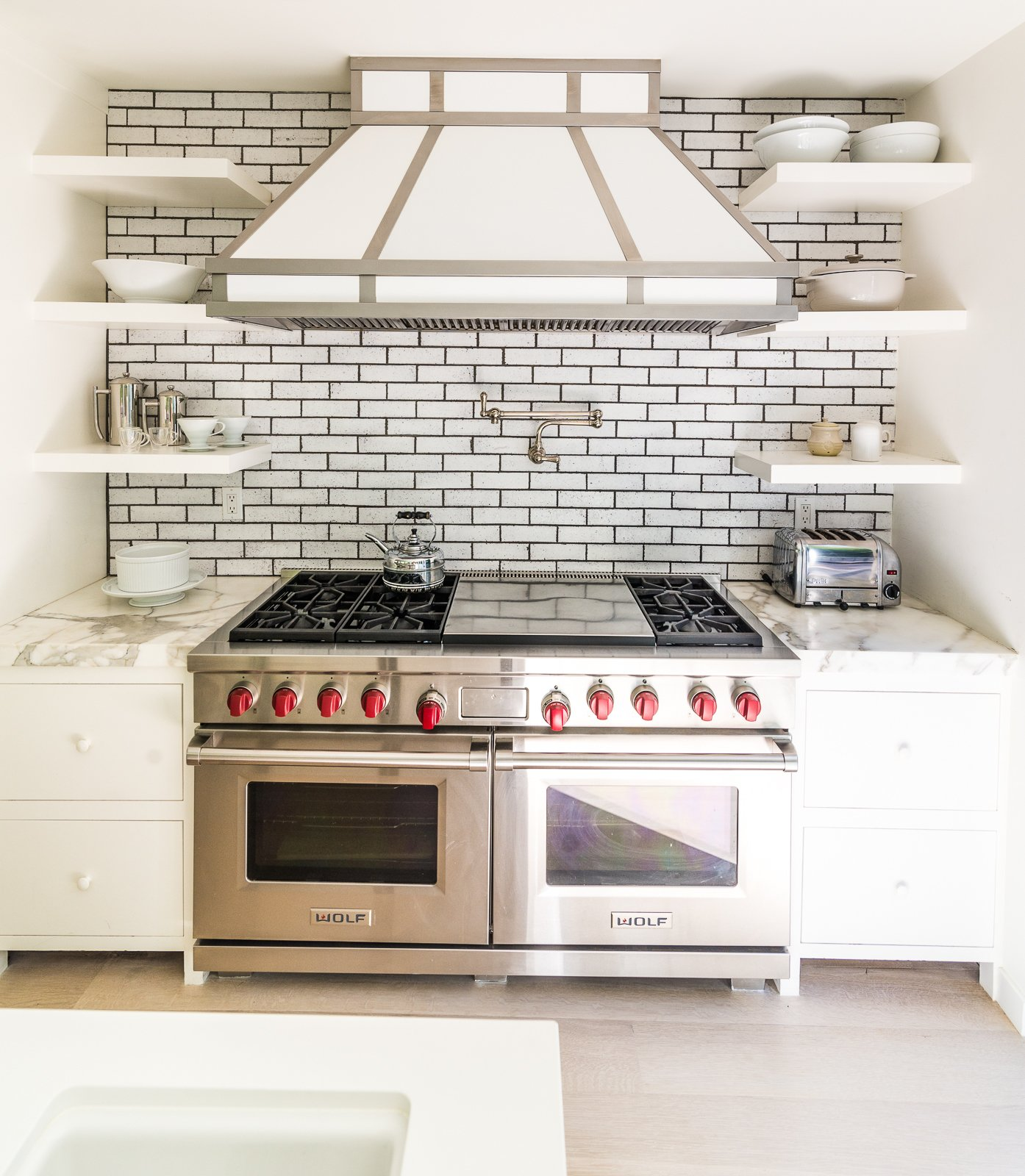 Calcutta marble adorns this beautiful stove top with dual oven and built in shelves  Nichols Canyon