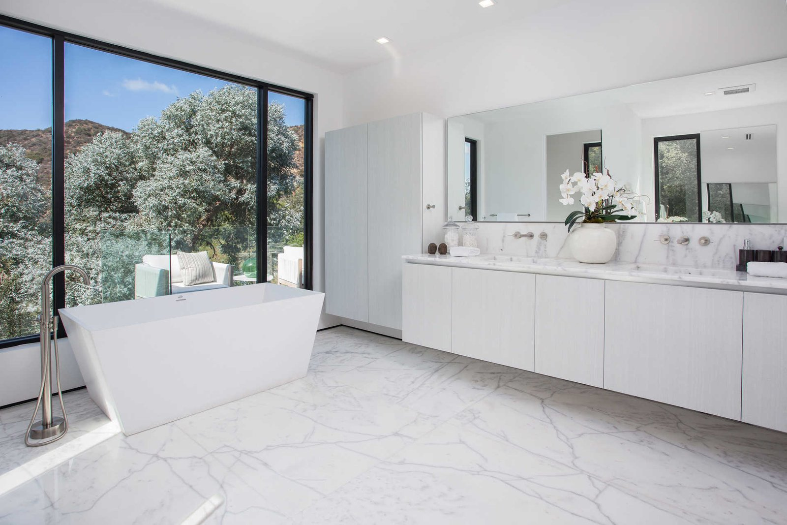 An elegant bathroom with standalone tub overlooks the hills.  Cherokee Contemporary