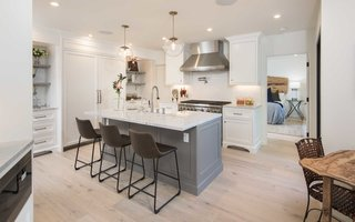 The remodeled and remastered chef's kitchen features integrated Thermadore refrigeration, a Wolf range, center Carrara slab island and custom built-ins.