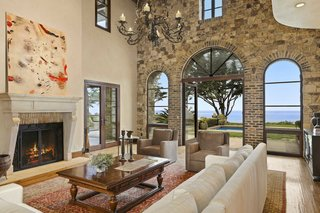 The soaring great room features a large fireplace and elegant arched windows opening to the pool and ocean beyond.