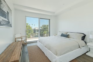 Bedroom suite with private terrace, abundant natural light and tree-lined views.
