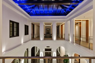 A 100-year old olive tree sits at the first floor of this atrium at the entry to a Beverly Hills mansion. On the second floor, the corridors of the second level open out to the level below, while a glass skylight above allows daylight to stream in.