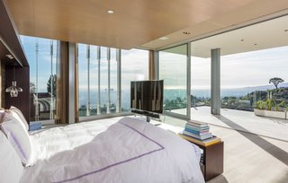 A glass-enclosed master suite is equipped with automatic shades and sliding glass doors to a large terrace that appears to float weightless over the lights of Los Angeles.