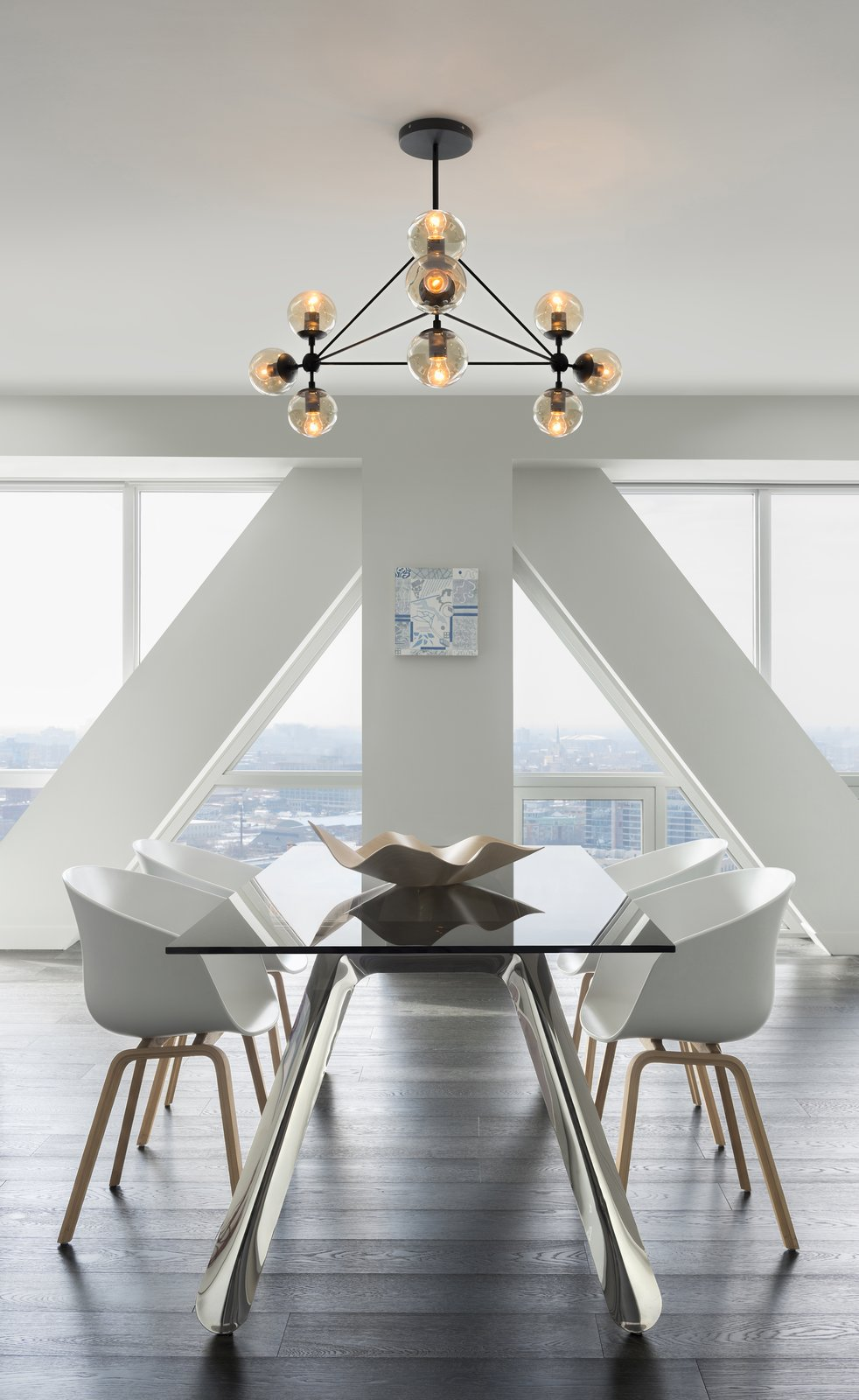 The geometric construction of the Bola suspension light gives this modern dining space bold contrast  Kitchen & Dining
