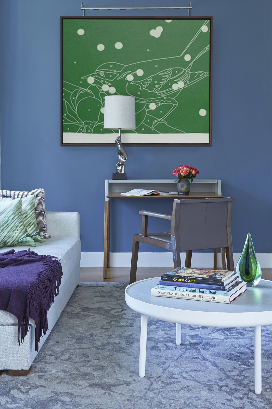 Guest rooms and dens should remain as beautiful as the rest of your home. Accents of color like this blue feature wall keep the room visually engaged and tie it to the now-connected living room. The Holly Hunt chair sits next to a desk lit by a mid-century Laurel table lamp that we replated.   Bachelor Pad