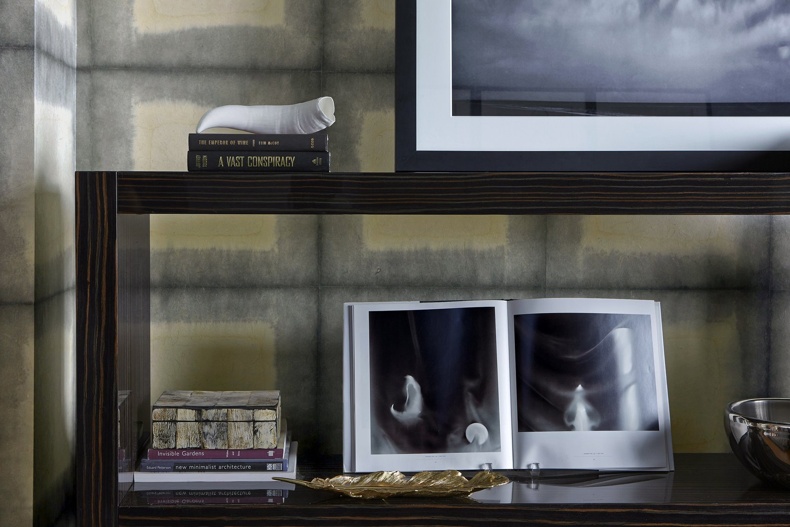 A rosewood Italian console from Minotti contrasts with handmade indigo Japanese wallpaper from Larsen. This beautiful shelving offers an area to display the client's books and vintage items.  Bachelor Pad