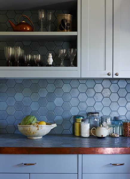 Cornflower blue hexagonal tiles form the backsplash in this blue kitchen, where the tiles continue onto the countertop (often a great way to save on your budget), which is edged in copper. The blue cabinets are a solid color in contrast to the variegated tones of the tiles.