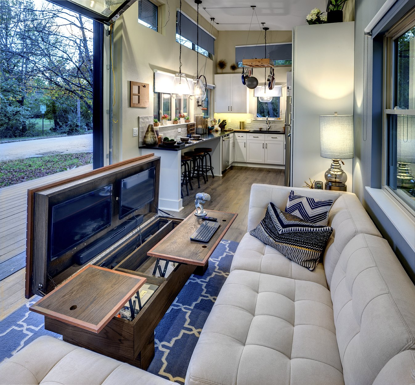 Living Room, Sofa, Sectional, End Tables, Coffee Tables, Table Lighting, Light Hardwood Floor, and Ceiling Lighting When this custom-made coffee table is open, it becomes a video editing desk with built-in drawers  Amplified Tiny House