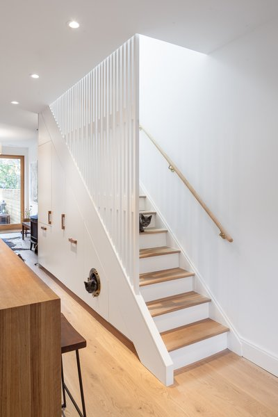 CAB Architects deftly hid appliances, pantry storage, and a litter box for the owners' two cats in the cabinetry beneath this staircase.