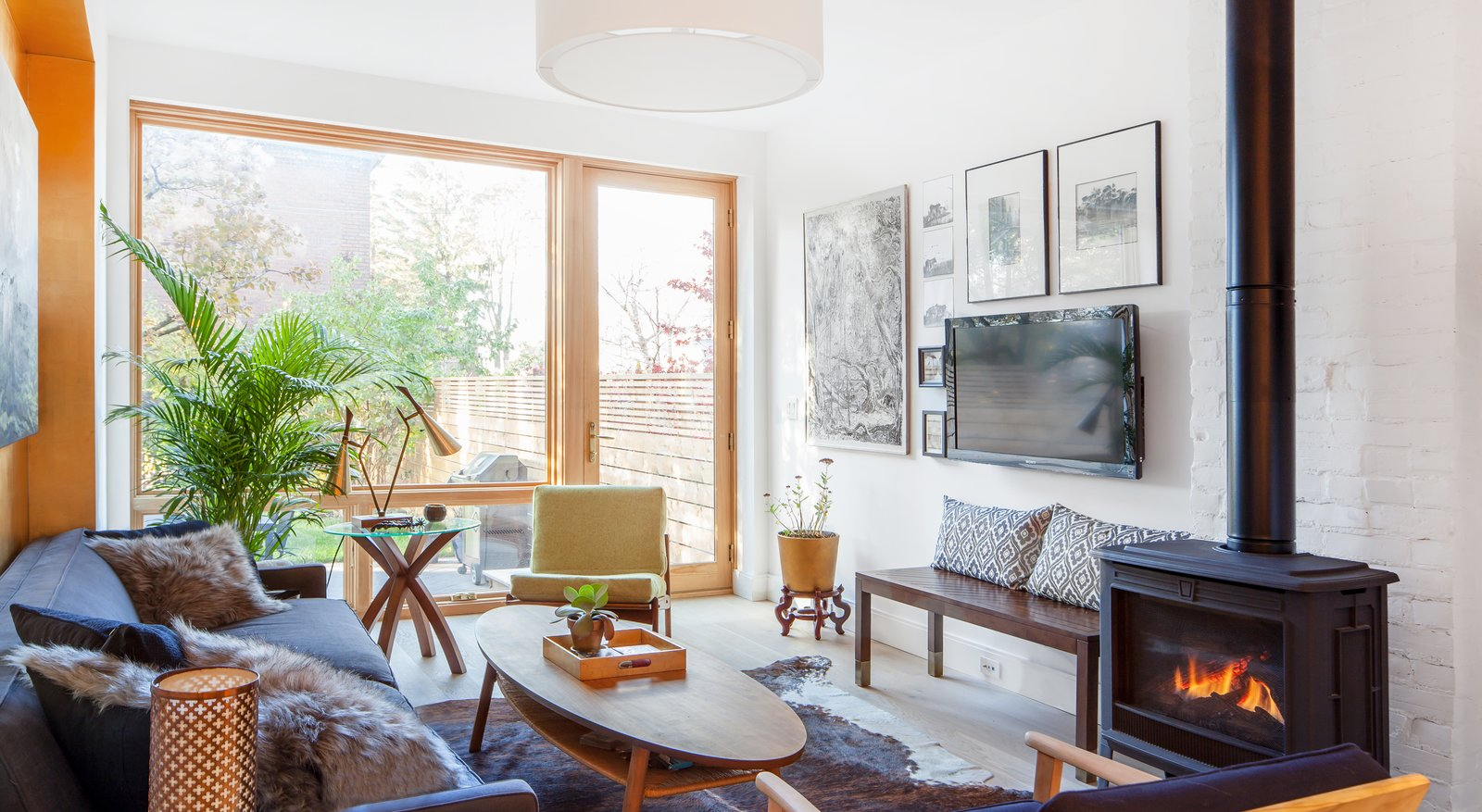 Living Room, Bench, End Tables, Sofa, Coffee Tables, Chair, Ceiling Lighting, Light Hardwood Floor, Gas Burning Fireplace, and Rug Floor Living room  Ritchie Rowhouse by CAB Architects