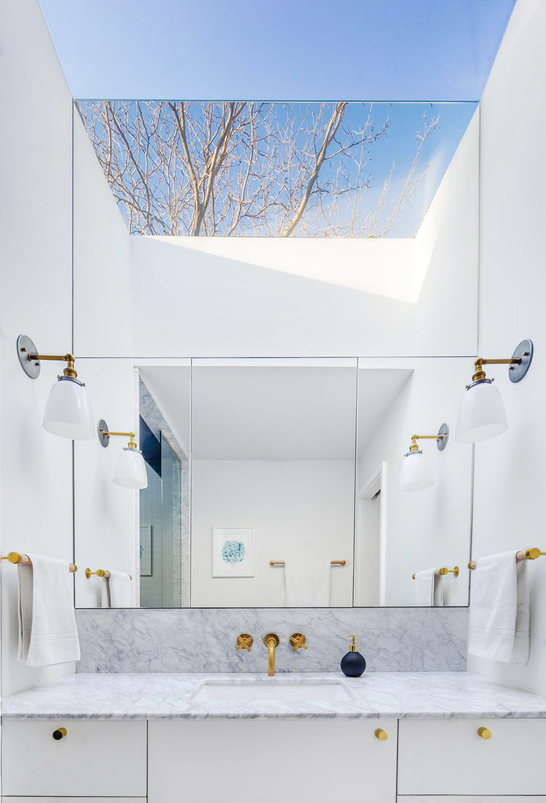 Bath Room, Marble Counter, Marble Floor, Undermount Sink, Marble Wall, One Piece Toilet, Wall Lighting, and Accent Lighting Master bath with reflected skylight  Best Photos from Ritchie Rowhouse