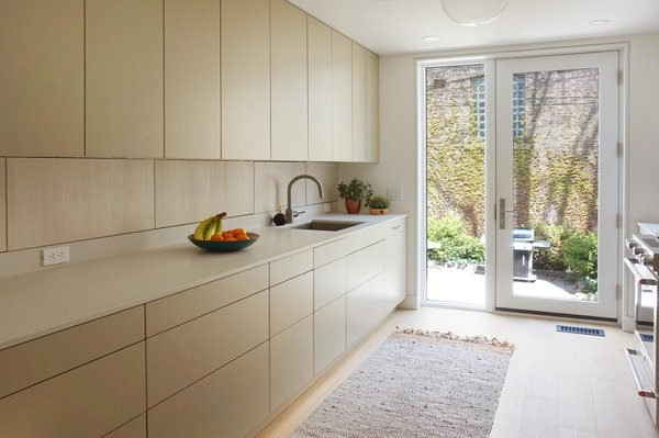 The material palette of this kitchen is calm and muted, using putty coloured cabinet doors, wood grain on the intermediate cabinets, a concrete coloured honed quartz countertop, and light oak flooring throughout.