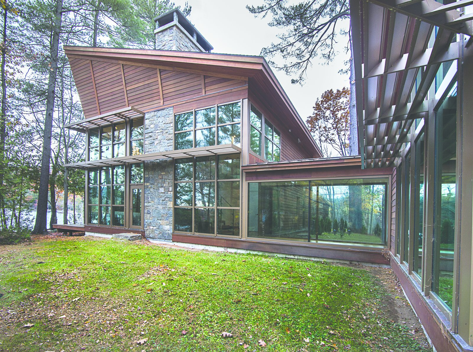 This lake house was designed in close collaboration with the client, an architect known for his architectural renderings and illustrations.  The exterior walls of the building were clad with glass to permit the site and the interior to act as one.  Modern Adirondack Retreat