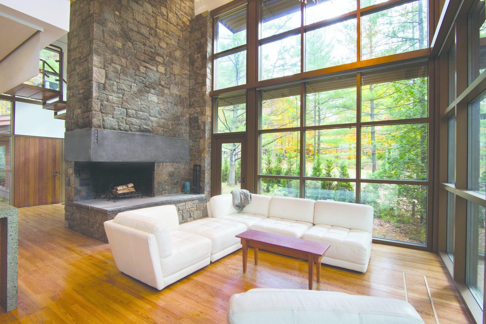 A cantilevered masonry fireplace opening with interlocking bluestone lintels continues the strong linear lines.  Modern Adirondack Retreat