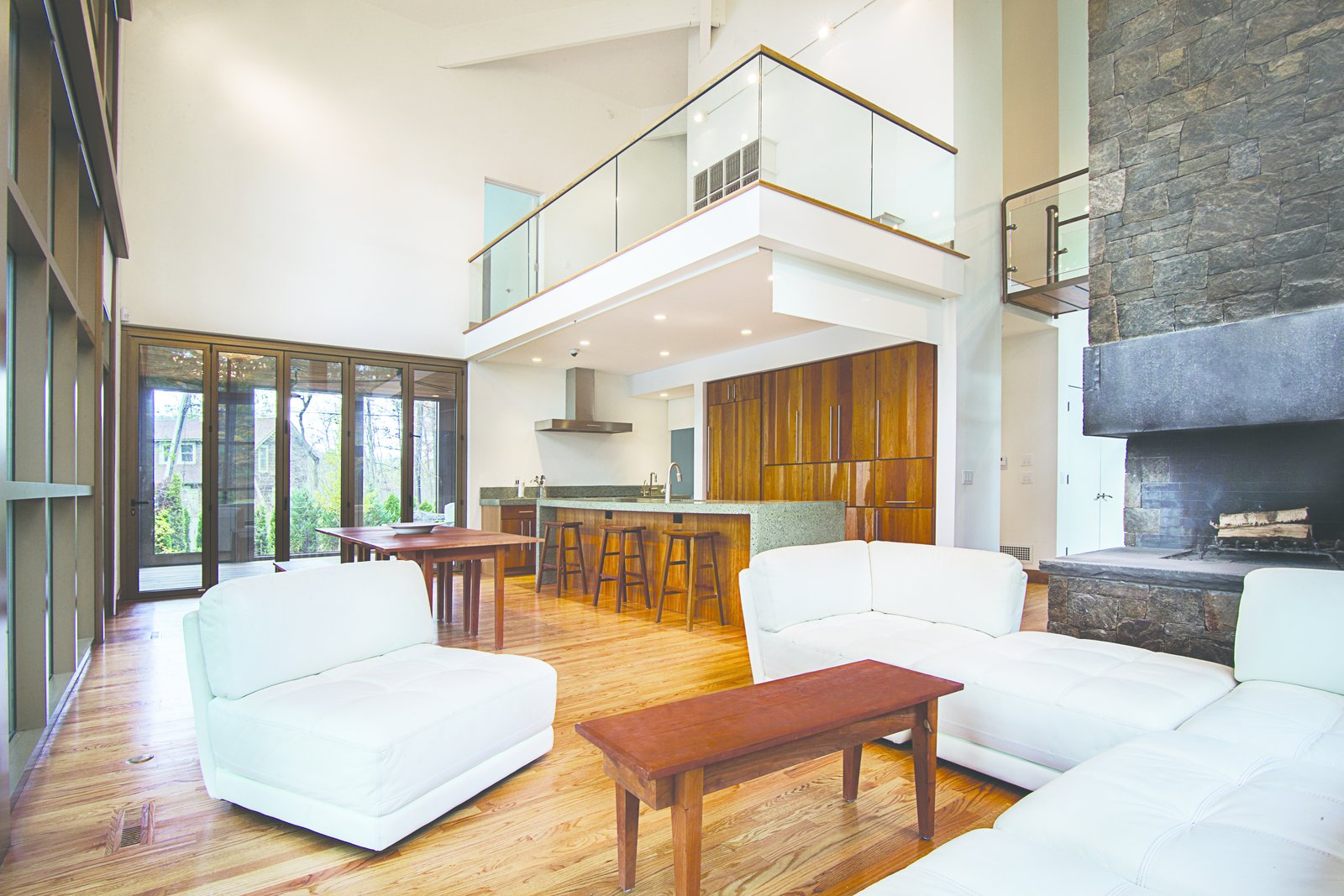 The 8' cantilevered mezzanine hovers over the kitchen area creating a more intimate space.  Modern Adirondack Retreat