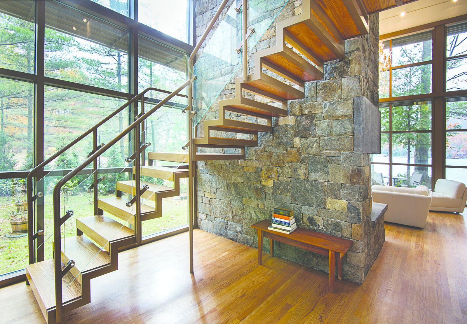 The sawtooth open staircase is anchored to granite chimney providing views of the stone through the stairway as well as, outside through the large glass wall behind the stair.  Modern Adirondack Retreat