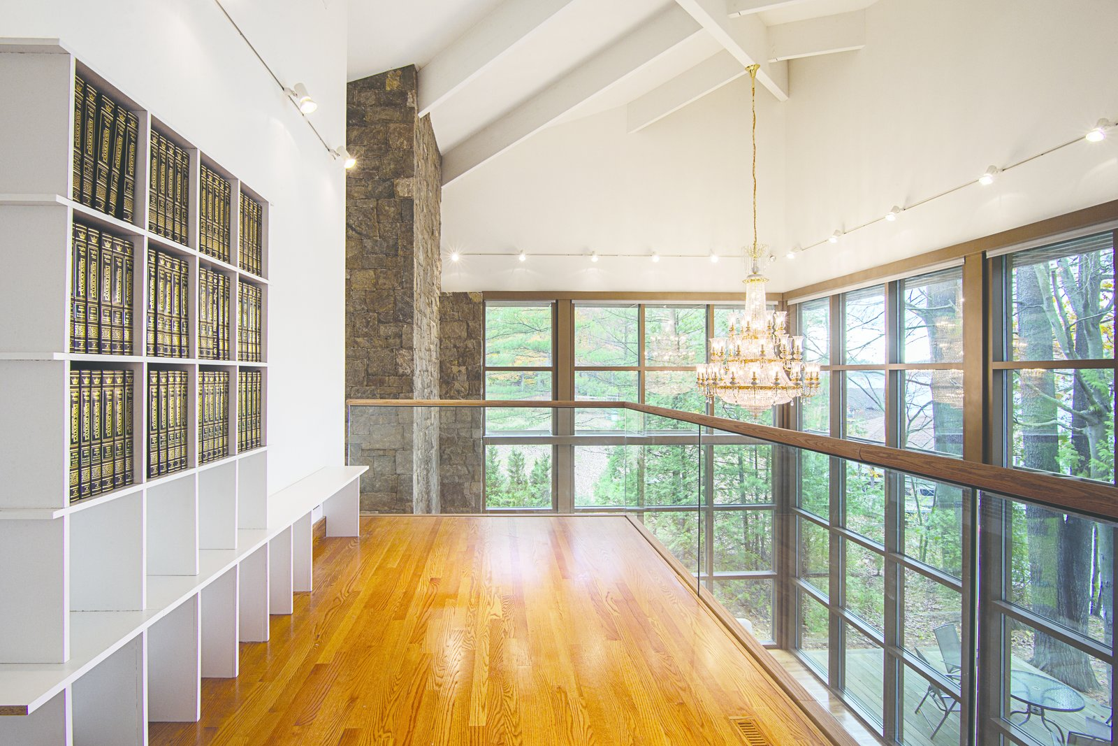 Execution of the details of the building reflected a minimalist approach desired by the home owners. This included the use of glass railing systems inside and the anchoring of each pavilion with a massive fireplace rendered in local granite.  Modern Adirondack Retreat