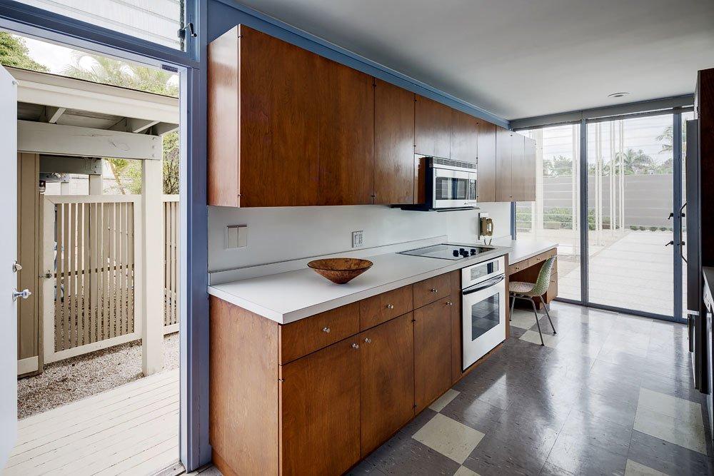 Kitchen, Laminate Counter, Wood Cabinet, Range, Linoleum Floor, Microwave, and Recessed Lighting Umbrella House, kitchen  Umbrella House