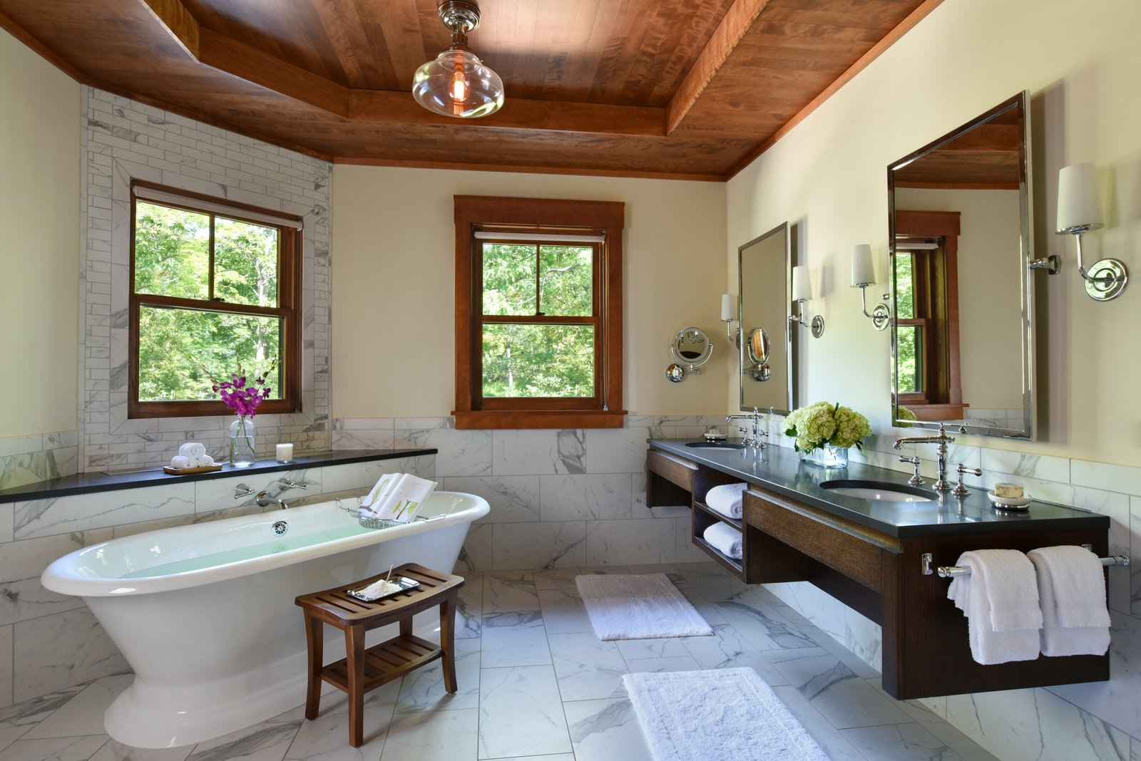 The 7,000-square-foot two-story Grove Lodge incorporates the use of native stone and natural finishes to help it blend into the scenic landscape of the Mohonk Mountain House property.  Interior spaces include hardwood floors and the use of exposed wood throughout. The guest rooms have their own separate drive-up entrances and feature either a stone patio (lower level) or balcony area. All areas are appointed with our rustic rocking chairs for outdoor seating.  Eco-friendly features include sustainable building materials, LED lighting, and a geo- thermal heating and cooling system. 250-tons of Shawangunk conglomerate excavated from the site have been recycled into the retaining walls and the stone fireplace.  Grove Lodge at Mohonk Mountain House by AJA Architecture and Planning