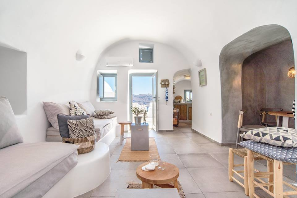 Living Room, Bench, Wall Lighting, and Limestone Floor Carved into the majestic Caldera cliffs of Santorini's most famous village – Oia, this yposkafo was renovated in 2016 and comes with an indoor and outdoor and an inviting interior decorated in soft greys and blues.  Photo 8 of 11 in Ever Wanted to Stay in a Cave That's Actually Pretty Modern Inside?