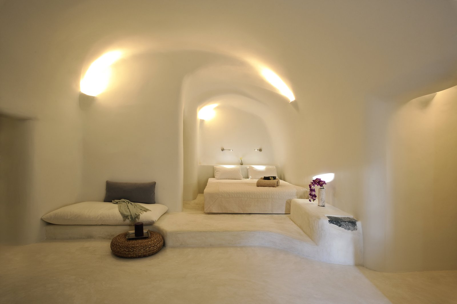 Bedroom, Bed, Concrete Floor, Bench, and Ceiling Lighting Kapari Natural Resort in the 300 year old village of Imerovigli on Santorini is pure bliss for those who like their interiors in white and earthy neutrals. The unique style of cycladic architecture comes through beautifully in the organic lines of the smooth-edged walls, floors and ceilings.  Photo 9 of 11 in Ever Wanted to Stay in a Cave That's Actually Pretty Modern Inside?