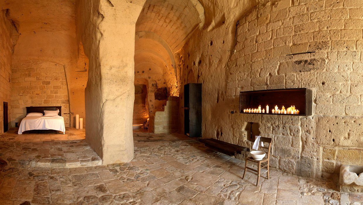Bedroom, Bed, and Chair Located in the UNESCO World Heritage cave village of Sassi de Matera in Southern Italy, Sextantio Le Grotto Della Civita is furnished with rustic, Zen-like pieces to allow the interesting textures and medieval magic of its cave setting to shine through.  Photo 11 of 11 in Ever Wanted to Stay in a Cave That's Actually Pretty Modern Inside?