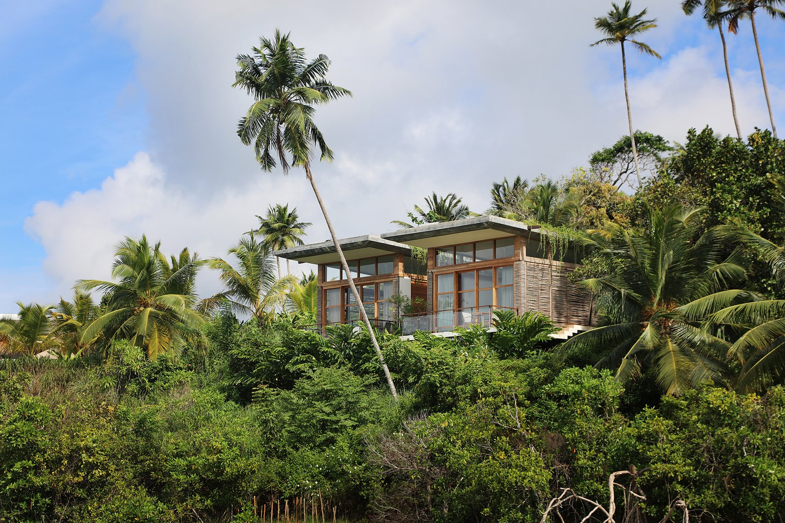 Exterior, Glass Siding Material, Flat RoofLine, and Wood Siding Material Surrounded by Lake Koggala, TRI Hotel is a sustainably built resort Sri Lankan resort with green walls and roofs, recycled wood furniture and solar heating that offers spectacular 360-degree views of verdant rainforests and the lake.  Photo 3 of 11 in Escape to the Jungle in One of These Modern Forested Retreats