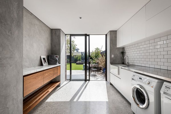 Australian studio Keen Architecture designed this large laundry room with minimalist grey walls, subway tiles splashback, built-in cabinetry and a large window that opens out to the garden, perfect for clothes in need of sun-drying.