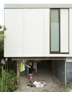 The homeowners of this New Zealand home have found a practical and passively sustainable alternative to a dryer as they hang their clothes out to dry in the ventilated space beneath the first floor of their house.