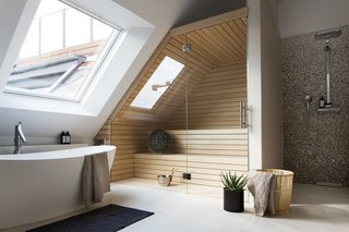 This converted attic in a turn-of-the-century building in Berlin's Charlottenburg neighborhood has a large skylight on the side-slope of the roof, which allows one to look up at the sky while having a relaxing soak.