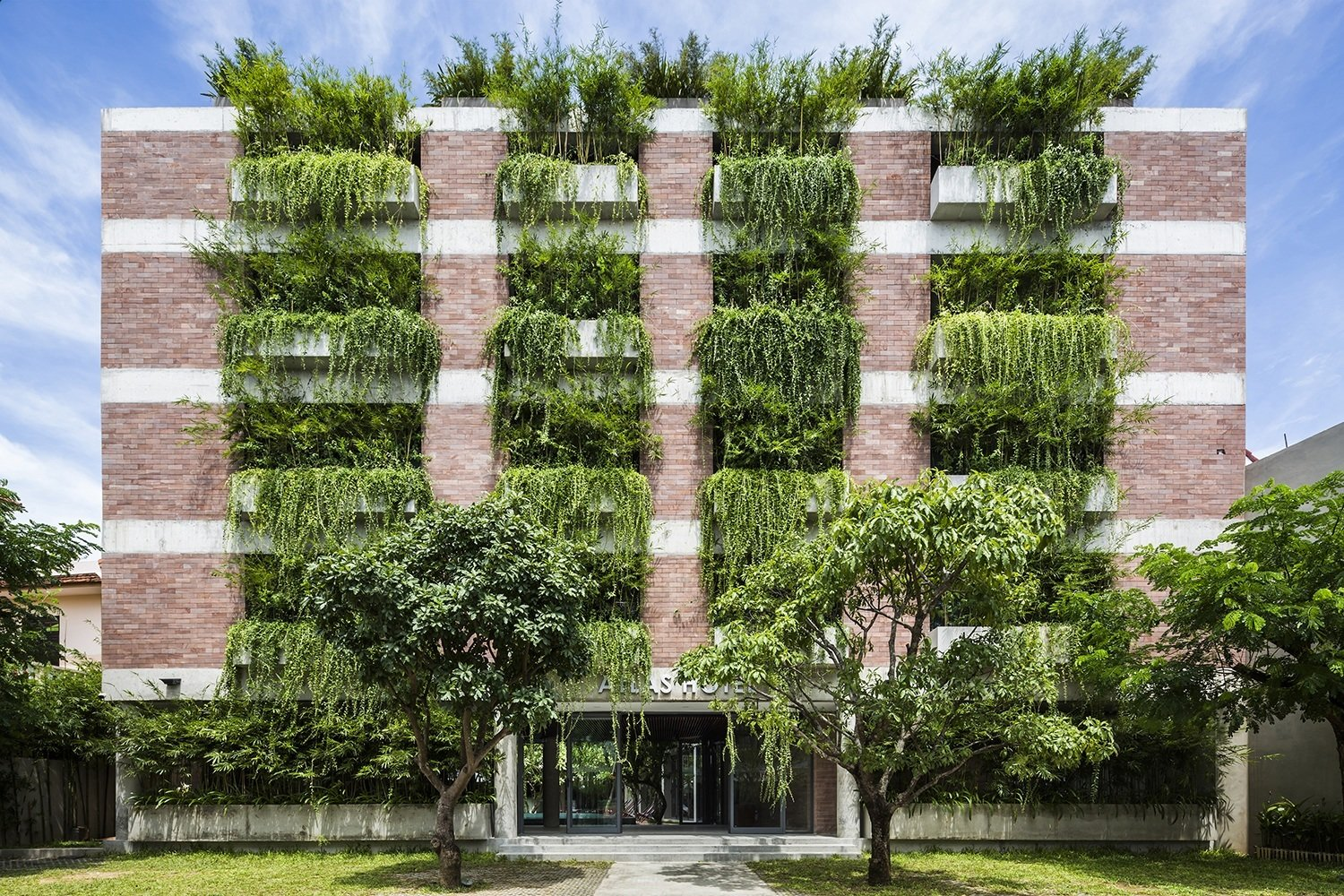Designed by sustainable Vietnamese practice Vo Trong Nghia, the Atlas hotel in Hoi has more that 100 cantilevered concrete planters, so the trailing plants that overhanf from the façade's balconies create the effect of a green façade that shades the guest rooms from the strong sunshine.  Photo 4 of 10 in 10 Ways to Create an Uplifting Vertical Garden