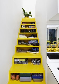 Architect Andrew Maynard's Melbourne home, which also doubles up as the office of his practice Austin Maynard Architects, includes a bright yellow staircase with opening slots in the front that serve as storage shelves.
