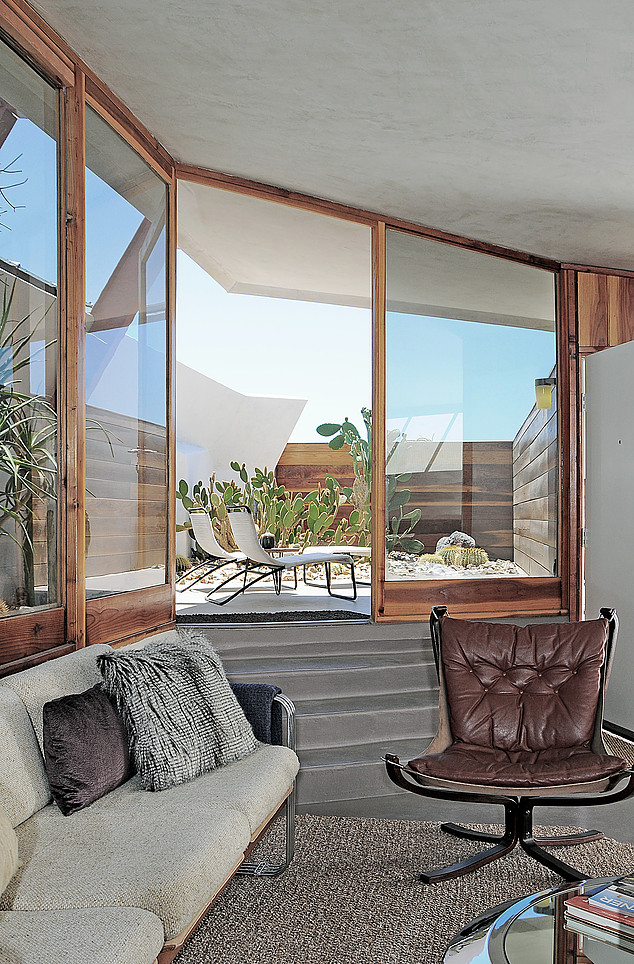 "Living Room, Sofa, Chair, Concrete Floor, Coffee Tables, and Carpet Floor ""We are a 'little slice of heaven' for any architecture, interior design, and midcentury modern aficionado,"" says Beckmann. The units are available for rent through Boutique Homes.  Photo 6 of 13 in Escape to a John Lautner Micro-Resort in the Californian Desert"