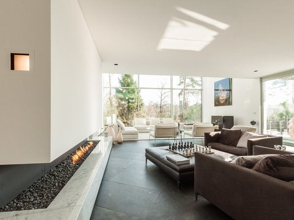 This six-bedroom villa in Brussels ha a cut-in stone fireplace underneath a glass-enclosed walkway.