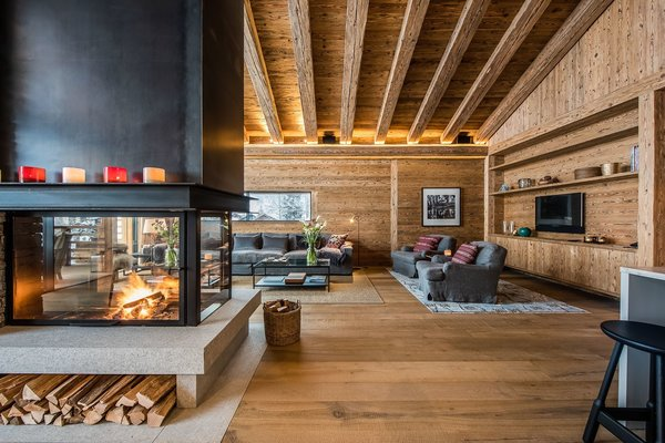 A contemporary glass-encased fireplace in this Zermatt villa acts as a partition that divides the living lounge from the dining area.