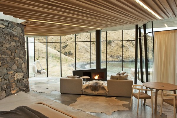 In this remote holiday rental home in New Zealand, guests can warm themselves by the asymmetrically shaped fireplace while looking out to views of a gorgeous, deserted by.