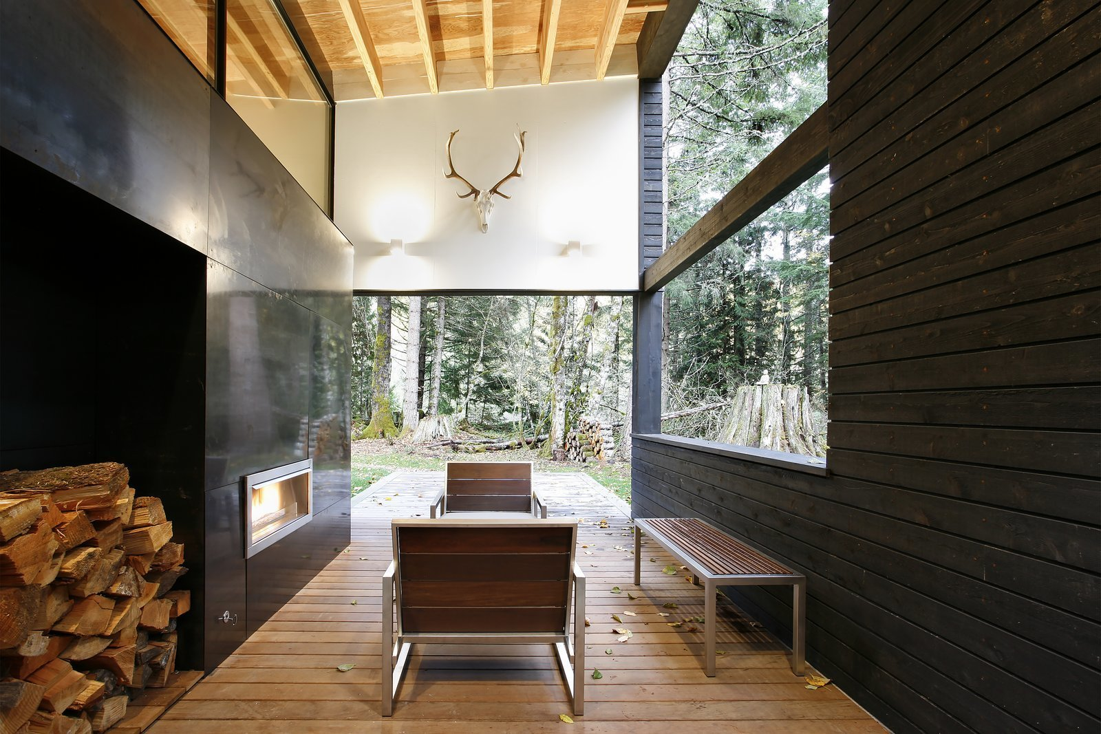Living Room, Bench, Chair, Wood Burning Fireplace, Ribbon Fireplace, Medium Hardwood Floor, and Wall Lighting In Greenwater, Washington, a courtyard house on a river was designed with a steel-clad fireplace mass that separates the living room from a covered outdoor patio.  Best Photos from 10 Modern Fireplaces That Make For Inviting Interiors