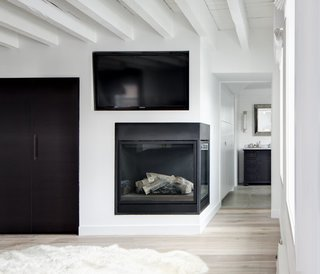 SU11 Architecture+Design designed this Grand Street loft in New York with a sleek, minimalist corner fireplace with glass panels on two sides.